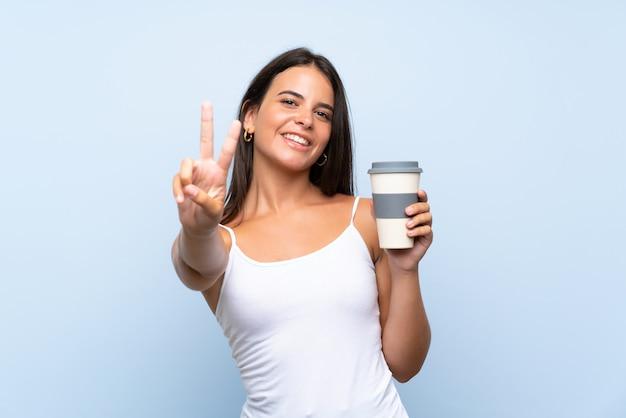 Młoda kobieta trzyma wynos kawę nad odosobnioną błękit ścianą uśmiecha się zwycięstwo znaka i pokazuje