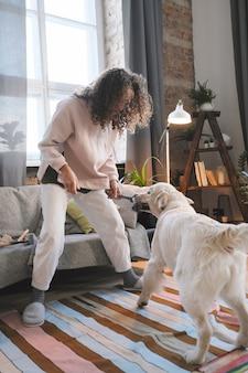 Młoda kobieta trzyma zabawkę i bawi się ze swoim zwierzakiem w pokoju
