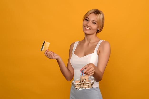 Młoda kobieta trzyma zabawkowy metalowy koszyk z niebieskim plastikowym uchwytem i kartą kredytową na białym tle. wizerunek