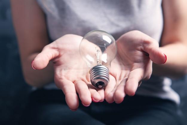 Młoda kobieta trzyma żarówkę. pomysły koncepcyjne