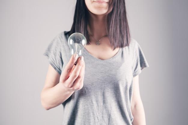 Młoda kobieta trzyma żarówkę
