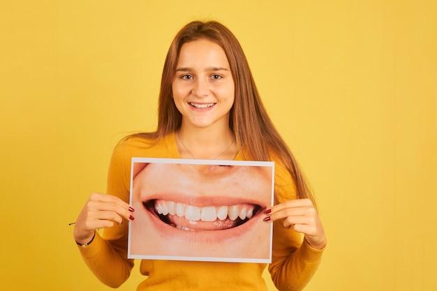 Młoda kobieta trzyma zdjęcie z uśmiechem usta, pokazując zęby na żółtym tle. koncepcja dentysty