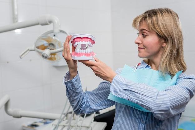 Młoda kobieta trzyma zęby zabawka
