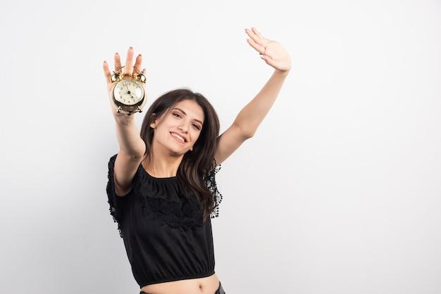 Młoda kobieta trzyma zegar