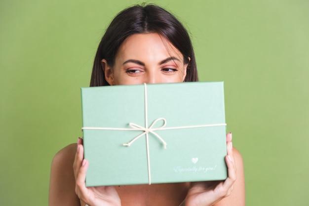 Młoda kobieta trzyma zielone pudełko na prezent