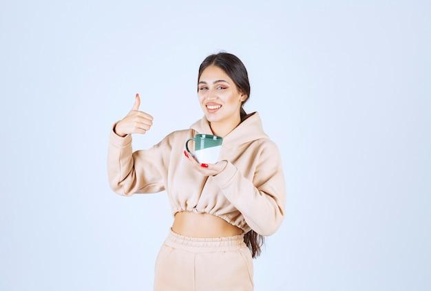 Młoda kobieta trzyma zielony kubek i pokazuje jej satysfakcję