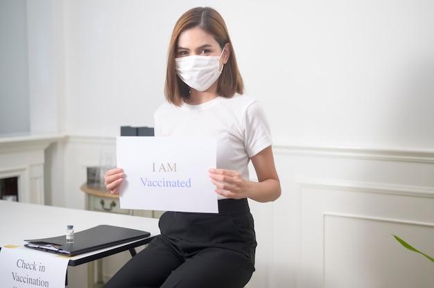 """Młoda Kobieta Trzyma Znak """"jestem Zaszczepionym"""", Koncepcja Szczepień Przeciw Covid-19 I Opieki Zdrowotnej Premium Zdjęcia"""