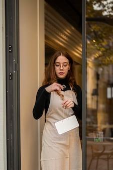 Młoda kobieta trzyma znak sklepu