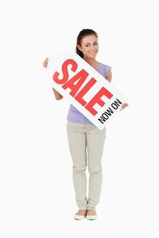 Młoda kobieta trzyma znak sprzedaży