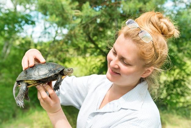 Młoda kobieta trzyma żółwia w rękach nad zielonymi drzewami