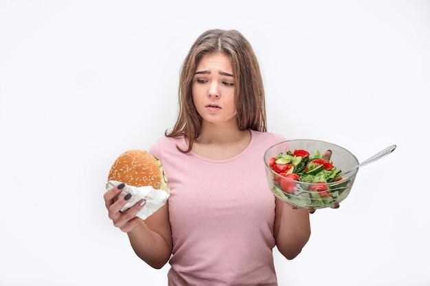 Młoda kobieta trzymać burger i szklaną miskę sałatki. patrzy na śmieciowe jedzenie. wątpliwości modelowe. na szarym tle.