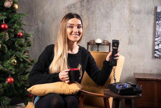 Młoda kobieta trzymając herbaty i telefon obok choinki.