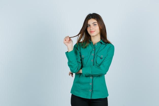 Młoda kobieta trzymając kasztanowe włosy palcami w zielonej koszuli i patrząc wesoło, widok z przodu.