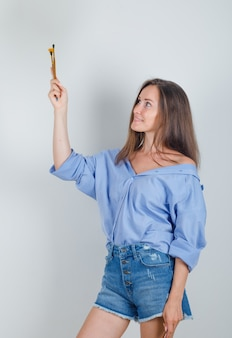 Młoda kobieta trzymając pędzle i uśmiechając się w koszuli