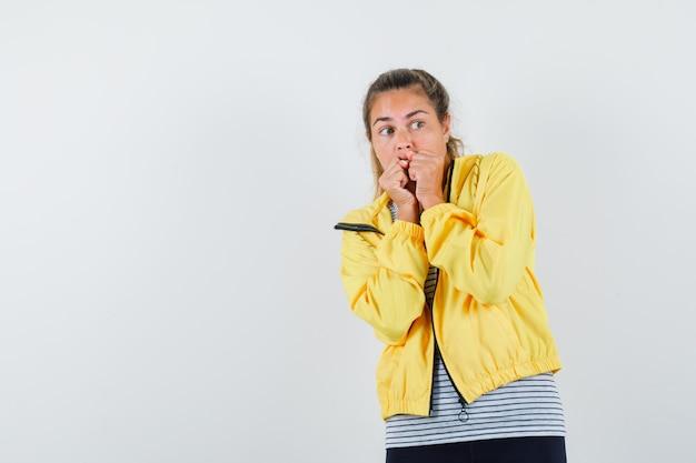 Młoda kobieta, trzymając pięści na ustach w koszulce, kurtce i patrząc przestraszony, widok z przodu.