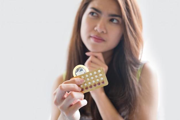 Młoda kobieta trzymając prezerwatywę i pigułki antykoncepcyjne zapobiegają ciąży
