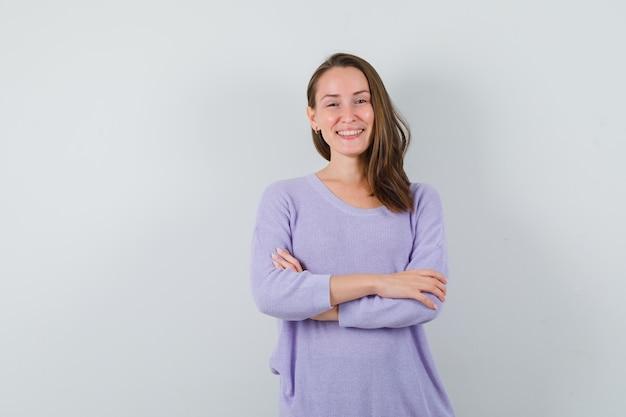 Młoda kobieta, trzymając ręce skrzyżowane, uśmiechając się w liliowej bluzce i patrząc jasno