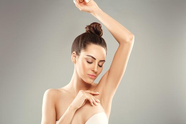 Młoda kobieta, trzymając ręce w górze i pokazując czyste pachy
