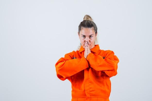 Młoda kobieta trzymając ręce w modlitwie gest w mundurze pracownika i patrząc bezradny. przedni widok.