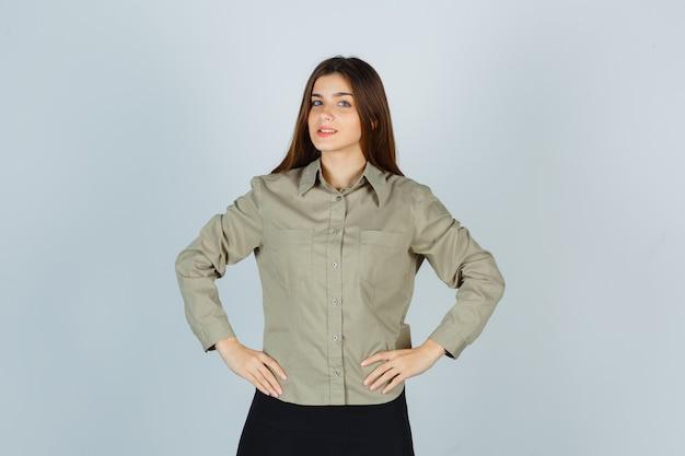 Młoda kobieta trzymając ręce w pasie w koszuli, spódnicy i patrząc pewnie. przedni widok.
