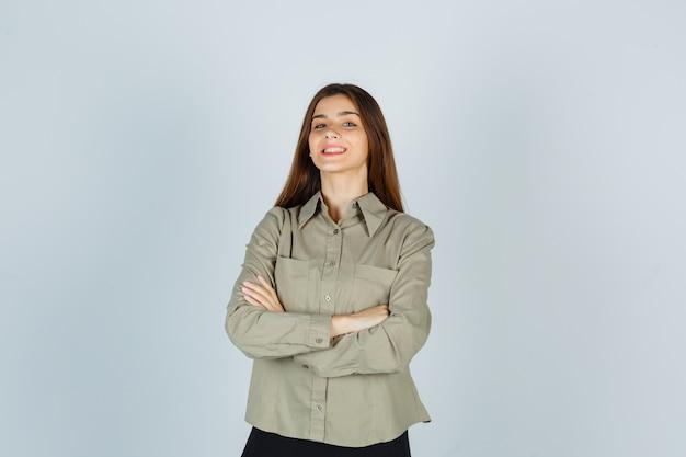 Młoda kobieta trzymając ręce złożone w koszulę, spódnicę i patrząc wesoło, widok z przodu.