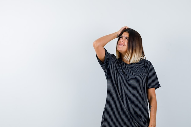 Młoda kobieta trzymając rękę na głowie, patrząc w górę w sukience polo i niepewny, patrząc z przodu.