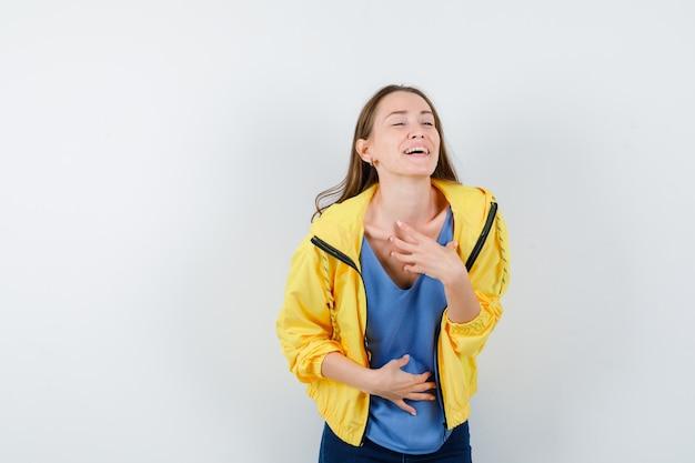 Młoda kobieta trzymając rękę na klatce piersiowej w t-shirt, kurtkę i patrząc szczęśliwy. przedni widok.