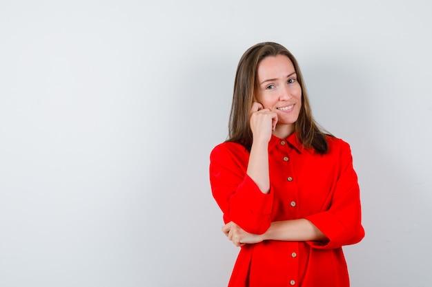 Młoda kobieta trzymając rękę na policzku w czerwonej bluzce i patrząc wesoło, widok z przodu.