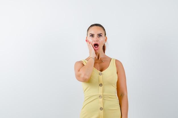 Młoda kobieta, trzymając rękę na policzku w żółtej sukience i patrząc w szoku