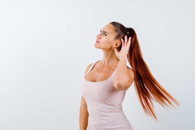 Młoda kobieta trzymając rękę za uchem w białym podkoszulku bez rękawów i patrząc zdziwiony, widok z przodu.
