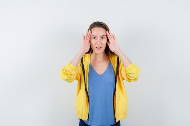 Młoda kobieta trzymając się za ręce, aby wyraźnie widzieć w koszulce, kurtce i patrząc zdumiona. przedni widok.