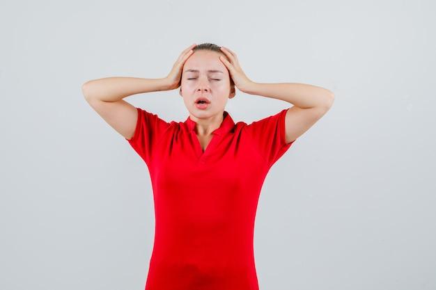 Młoda kobieta trzymając się za ręce do głowy w czerwonej koszulce i patrząc ostrożnie
