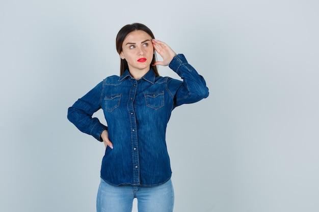 Młoda kobieta trzymając się za ręce na biodrze, trzymając rękę na skroniach w dżinsowej koszuli i dżinsach i patrząc zamyślony