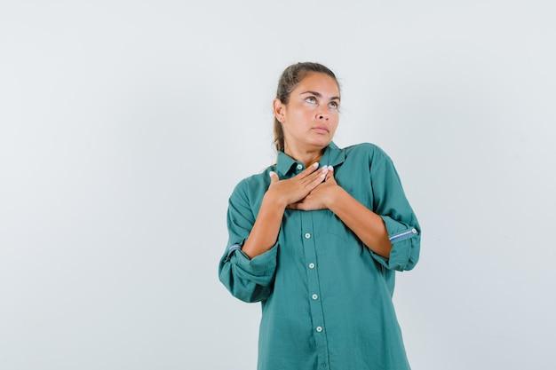 Młoda kobieta, trzymając się za ręce na klatce piersiowej w zielonej bluzce i wyglądający uroczo