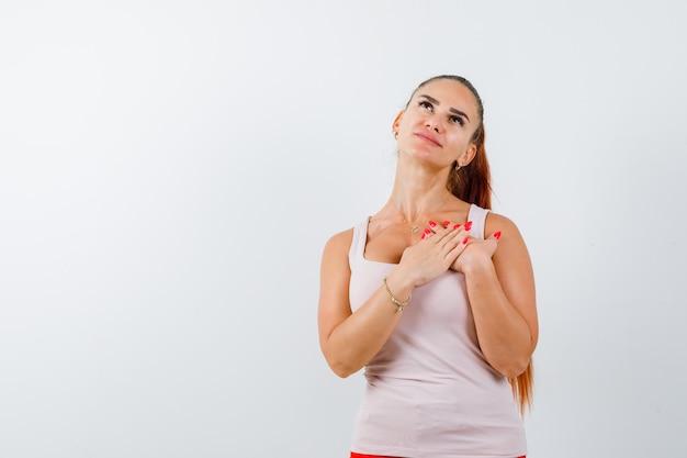 Młoda kobieta trzymając się za ręce na piersi do modlitwy w białym podkoszulku i patrząc z nadzieją. przedni widok.