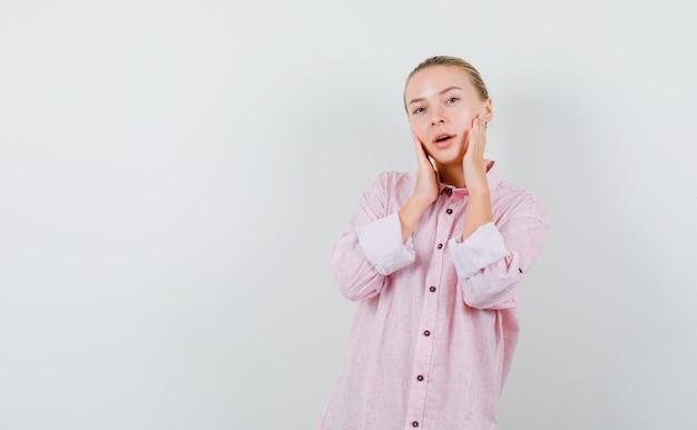 Młoda kobieta, trzymając się za ręce na policzkach w różowej koszuli i patrząc świeżo