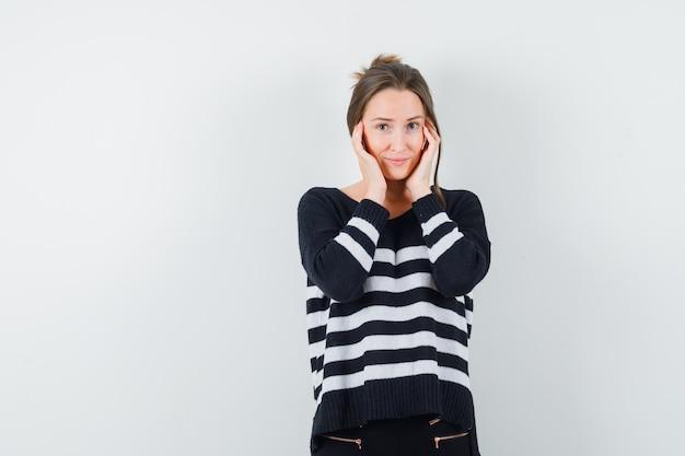 Młoda kobieta trzymając się za ręce na policzku w czarną bluzkę i czarne spodnie i patrząc uroczo