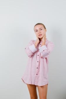 Młoda kobieta trzymając się za ręce na szyi w różowej koszuli i patrząc ponętnie
