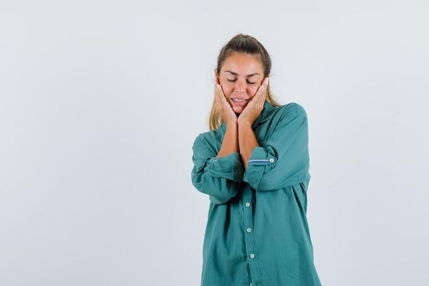Młoda kobieta trzymając się za ręce na twarzy w zielonej bluzce i patrząc szczęśliwy