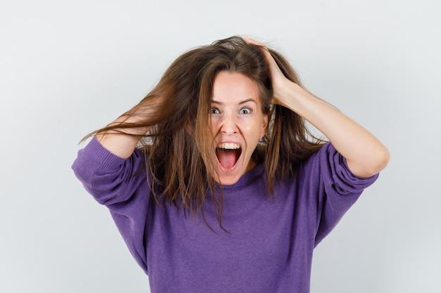 Młoda kobieta trzymając się za ręce na włosy w wełnianej koszuli i patrząc szalony, widok z przodu.
