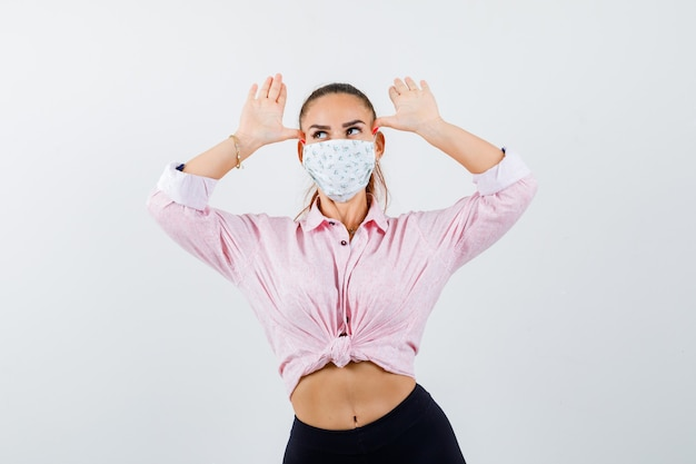 Młoda kobieta trzymając się za ręce nad głową jak uszy w koszuli, spodniach, masce medycznej i wyglądając śmiesznie. przedni widok.