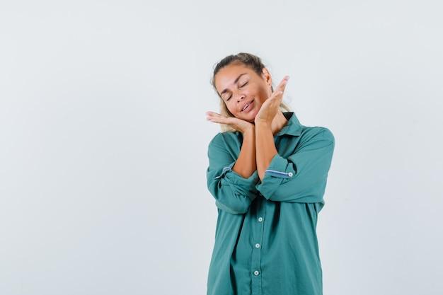 Młoda kobieta trzymając się za ręce pod brodą, zamykając oczy w zielonej bluzce i patrząc na szczęśliwego