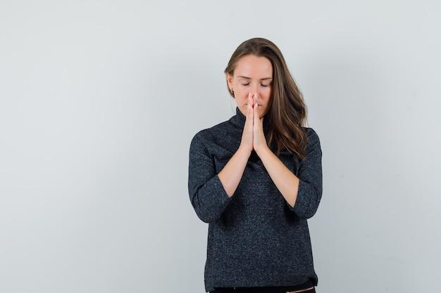 Młoda kobieta, trzymając się za ręce w geście modlitwy w koszuli i patrząc z nadzieją