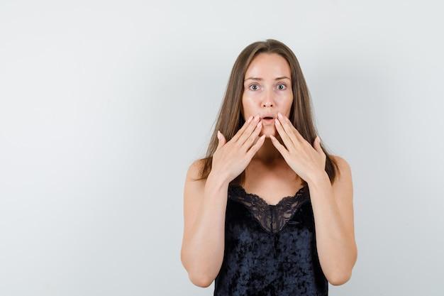 Młoda kobieta trzymając się za ręce w pobliżu ust w czarnym podkoszulku i patrząc zszokowana.