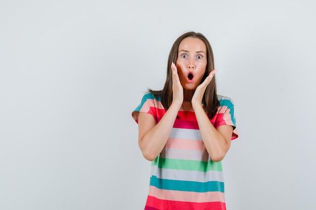 Młoda kobieta trzymając się za ręce w pobliżu ust w t-shirt i patrząc zszokowany, widok z przodu.
