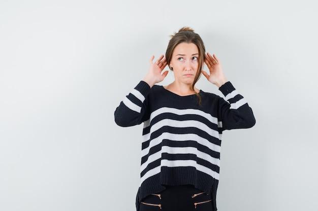 Młoda kobieta trzymając się za ręce w pobliżu uszu w dzianinie w paski i czarne spodnie i patrząc zamyślony