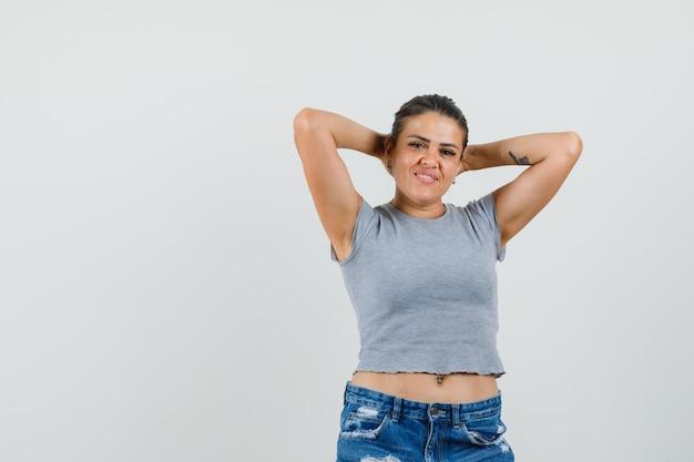 Młoda kobieta trzymając się za ręce za głową w koszulce, spodenkach i patrząc zrelaksowany