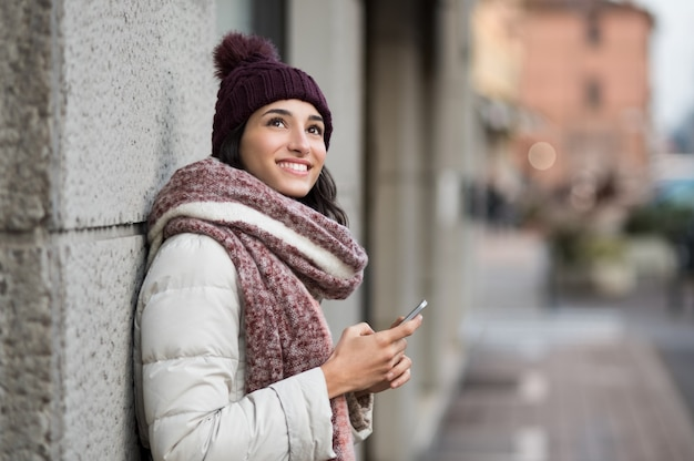 Młoda kobieta trzymając smartfon i patrząc w górę