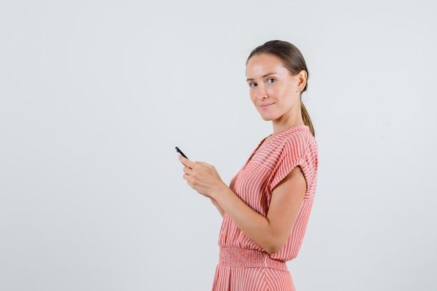 Młoda kobieta trzymając telefon komórkowy w paski sukienka i patrząc wesoło. .