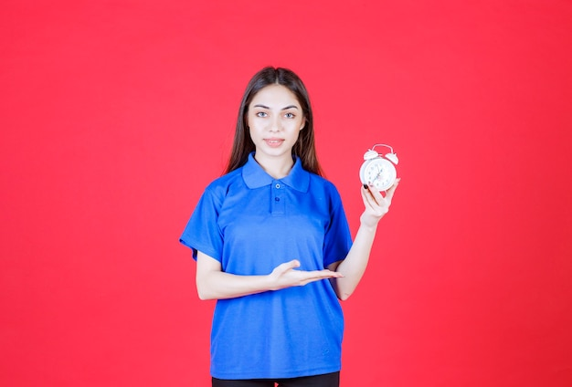 Młoda kobieta trzymająca budzik i wskazująca na niego